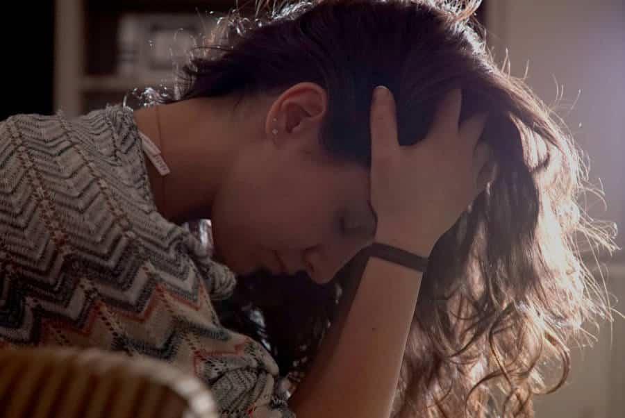Jonge vrouw met haar hoofd in haar handen