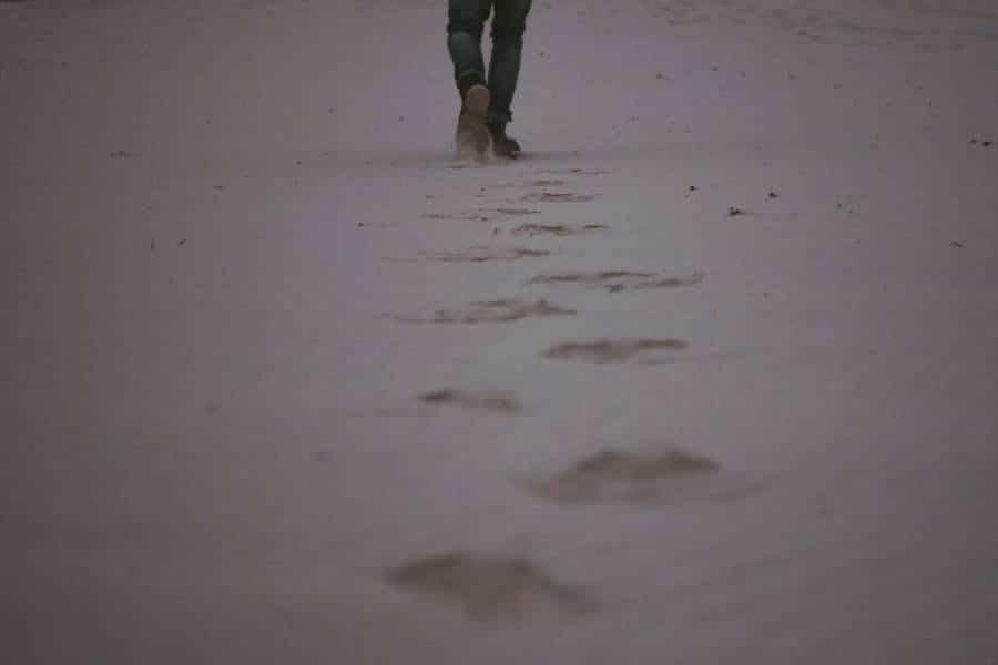 Voetstappen van iemand die alleen loopt in het zand