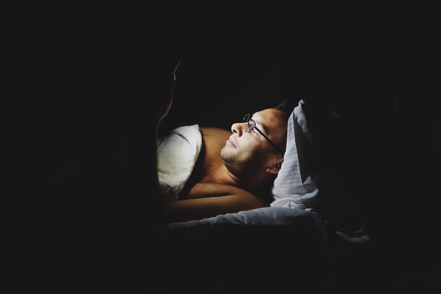 Man met slaap problemen ligt in bed in het donker met zijn mobiele telefoon